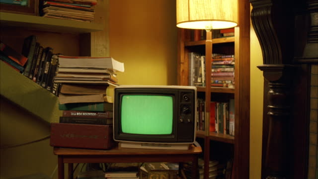 vídeos de stock, filmes e b-roll de ms zi small old style television set, located in corner of junky room (push into ecu of television green screen) - pilha arranjo