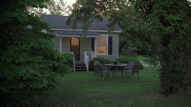 WS Small one story house with picnic table and chairs in yard