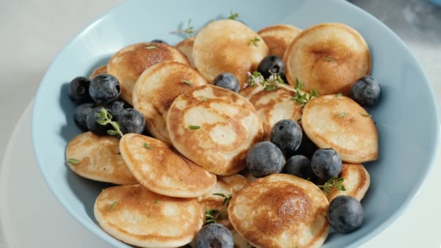 small pancakes or poffertjes with bluberries and thyme sprigs in blue bowl, dutch cuisine. rotating - blueberry stock videos & royalty-free footage