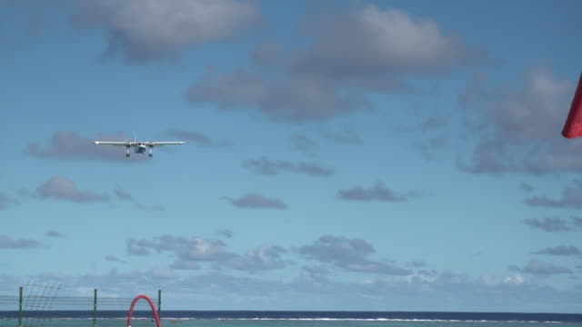 a small passenger airplane lands on an airport runway of tropical islands in french polynesia. - insel stock-videos und b-roll-filmmaterial