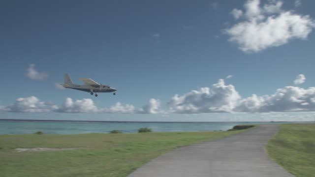 a small passenger airplane lands on an airport runway of tropical islands in french polynesia. - propeller stock videos & royalty-free footage
