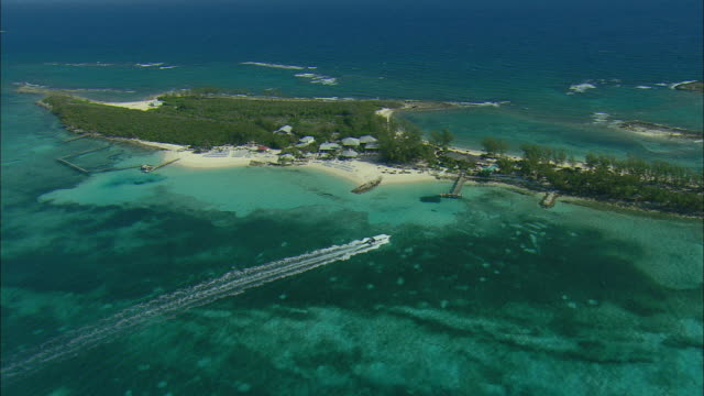 AERIAL Small passenger ferry boat arriving at a resort 'day-trip' island near Nassau, Bahamas
