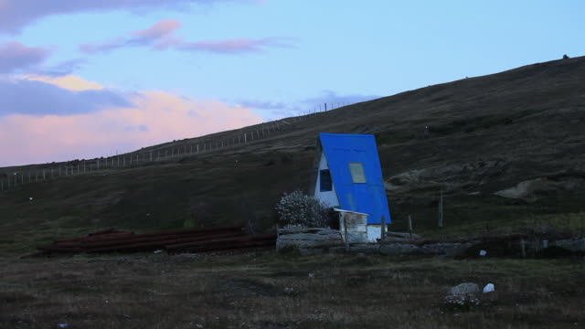 MS Small peculiar house with blue roof on dark green hill at nice late afternoon sky / Near Porvenir, Chilean Patagonia, Chile