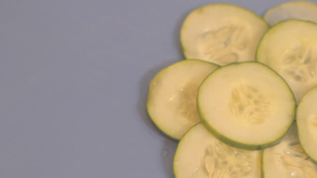 Small pile of cucumber slices sitting on a blue cutting board.