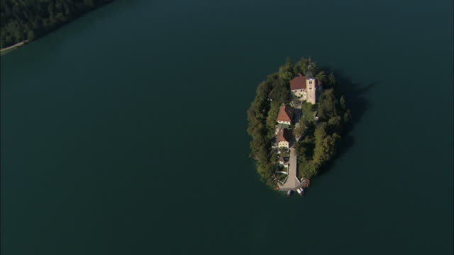 vídeos de stock e filmes b-roll de aerial small pilgrimage church of the assumption of mary on lake bled / slovenia - lago bled