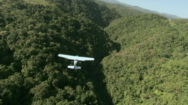 vídeos de stock e filmes b-roll de ts a small plane flying over a lush, tropical mountain range oahu, hawaii, united states - ilha