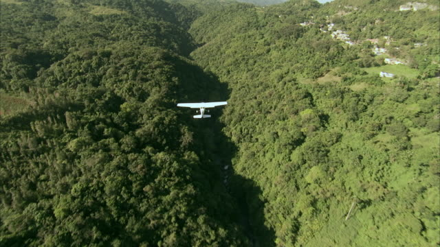 AERIAL Small plane flying over mountain tops / Hawaii, United States