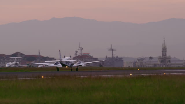 small plane gathers speed and takes off from the jacarepaguìá airport - プロペラ機点の映像素材/bロール