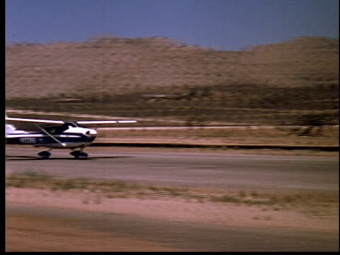 1965 film montage ws small plane landing on runway/ pan ms man greeting passengers as they disembark plane/ yucca valley, california - air vehicle stock videos & royalty-free footage
