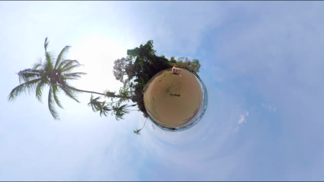 small planet effect of a man sitting on the beach - 360 video stock videos & royalty-free footage