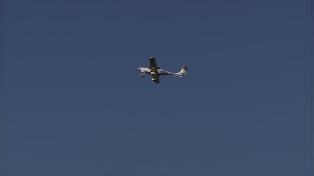 a small propeller plane flies in an almost clear sky. - プロペラ機点の映像素材/bロール