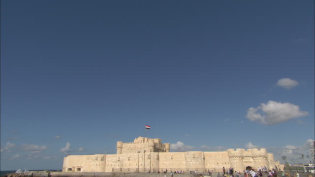 vidéos et rushes de small, puffy clouds float over the citadel of qaitbay in alexandria, egypt. - alexandrie