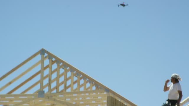 A Small Quadcopter Drone Flies over a Construction Site as a Male Construction Worker in His Forties Frames a House on a Clear, Sunny Day