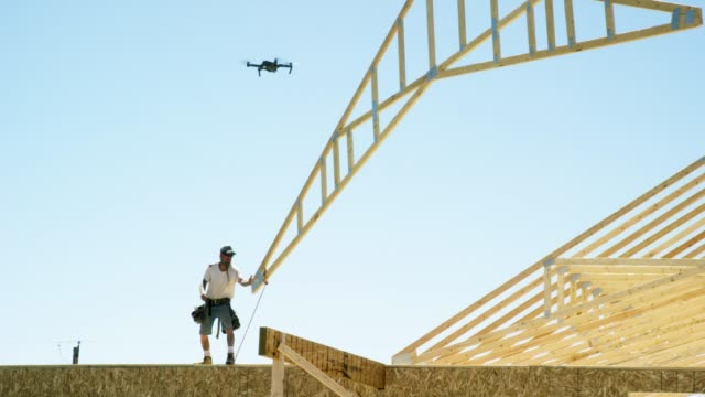A Small Quadcopter Drone Flies Overhead as a Hydraulic Crane Lowers a Framed Wooden Roof Truss to a Caucasian Male Construction Worker in His Forties Who Guides It into Place While Framing a House on a Clear, Sunny Day