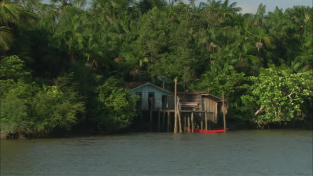 a small red canoe docks alongside a stilt-supported house. - stilt house stock videos & royalty-free footage