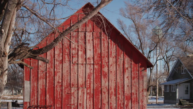 a small red weathered barn surrounded by bare trees in the middle of winter. - weathered stock videos & royalty-free footage