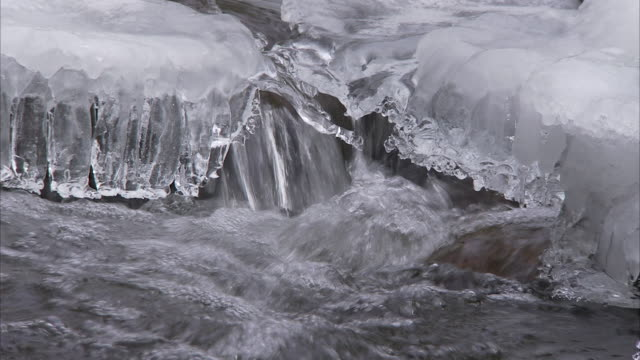 a small river cascade breaks through a crust of ice. - north america stock videos & royalty-free footage