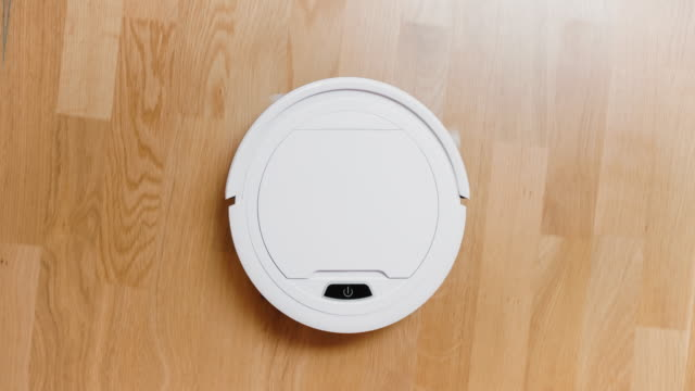 vídeos de stock e filmes b-roll de a small robot vacuum cleaner at home - equipamento