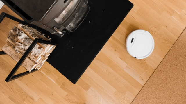 a small robot vacuum cleaner at home - cork material stock videos & royalty-free footage
