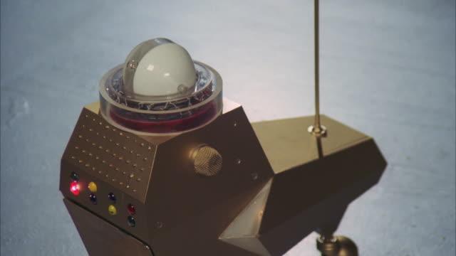 vídeos de stock e filmes b-roll de cu small robot with flashing multi colored lights moving on floor - 1977