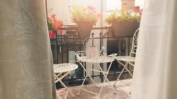 small romantic balcony with flower boxes and curtains blowing in the wind