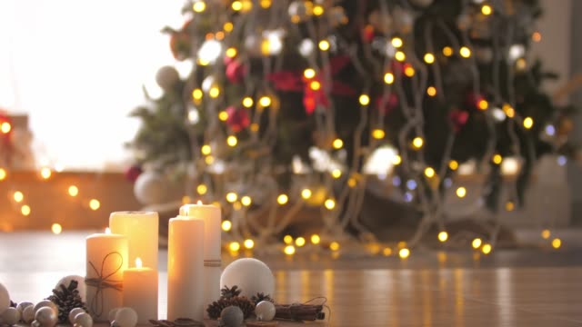 small rustic decoration of candles, pine cones and ornaments with a christmas tree in the background - christmas decore candle stock videos & royalty-free footage
