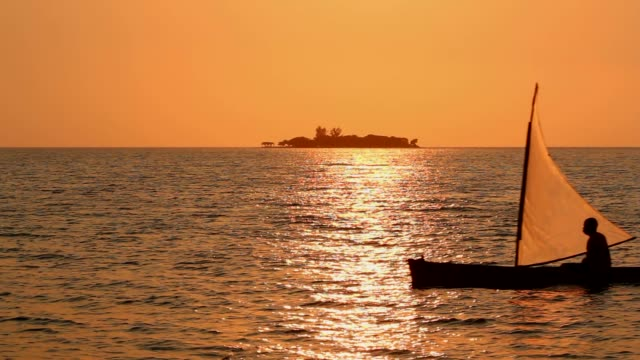 Small sailboat cross the sea at sunset