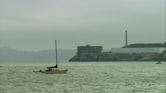 ws pan small sailboat crossing san francisco bay, alcatraz island in background, san francisco, california, usa - alcatraz island stock videos & royalty-free footage