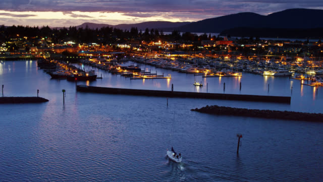 small sailboat pulling in to anacortes marina at night - drone shot - anacortes stock videos & royalty-free footage