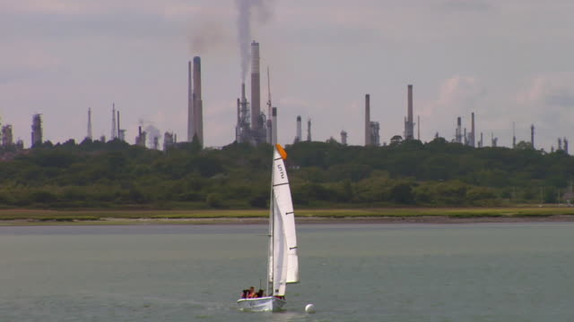 vídeos y material grabado en eventos de stock de ws small sailing boat on harbor, oil refinery in background, southampton, hampshire, united kingdom - hampshire