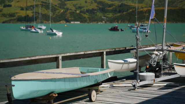 small sailing boats sit on a wooden jetty in a peaceful harbour - akaroa stock videos & royalty-free footage