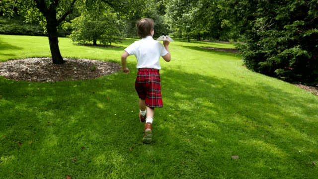 a small scotsman in a kilt plays with a toy airplane in the park - kilt stock videos & royalty-free footage