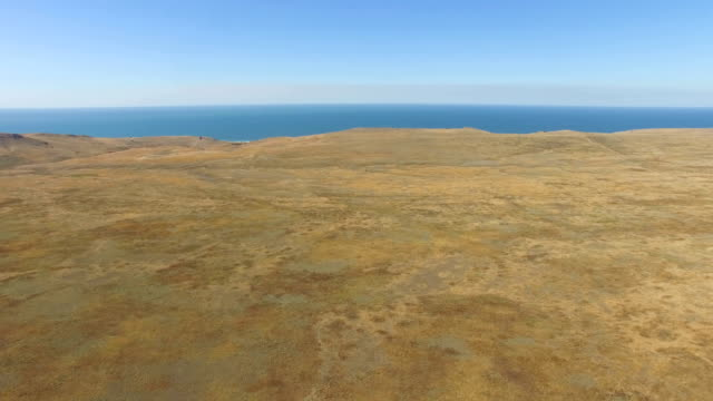 aerial: small sea island with plateau on steppe hills - orizzonte sull'acqua video stock e b–roll