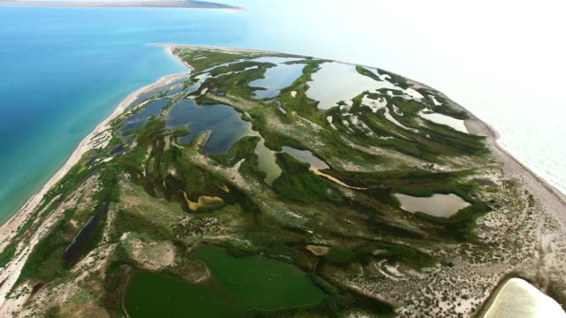 AERIAL: Small sea island with salt lakes and sandy white beach