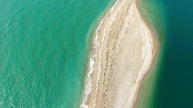 AERIAL: Small sea island with sandy white beach