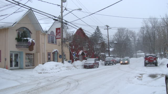 MS PAN Small ski town street in blizzard with cars moving on street  / Ellicottville, New York, Canada