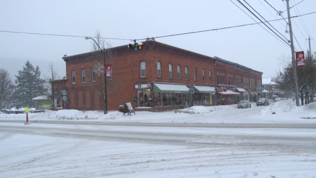 MS Small ski town street in blizzard with cars moving through intersection / Ellicottville, New York, Canada
