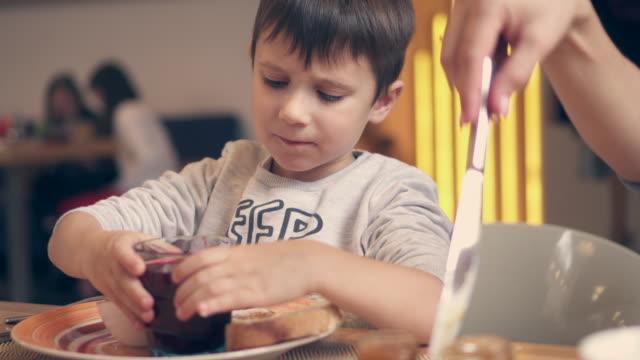 kleiner sohn und mutter im café sitzen und mittagessen - familie mit zwei generationen stock-videos und b-roll-filmmaterial