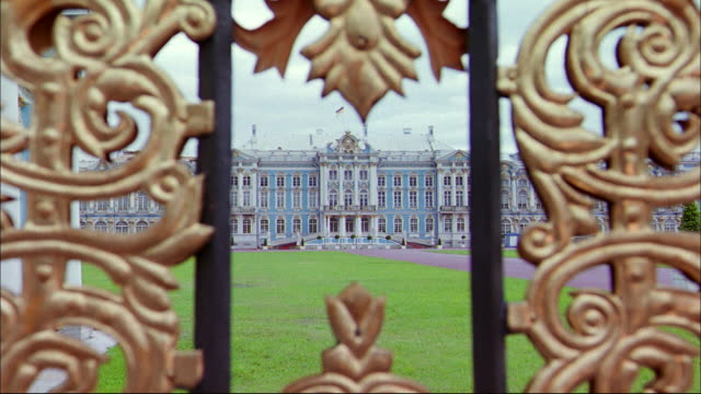 a small space in gold filigree gates frames the state hermitage museum in st. petersburg, russia. - sankt petersburg stock-videos und b-roll-filmmaterial