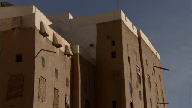 Small square windows scatter across a mud brick high rise.