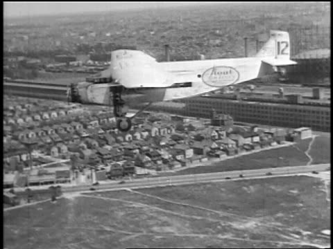 b/w 1927 aerial air-to-air small stout air lines airliner flying low over suburbs / newsreel - commercial aircraft stock videos & royalty-free footage