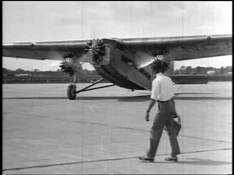 stockvideo's en b-roll-footage met b/w 1927 small stout air lines airplane taxiing on tarmac + door opening / newsreel - 1927