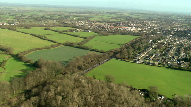 small suburbs lie within lush green farm fields in the british countryside. available in hd. - suburban stock videos & royalty-free footage