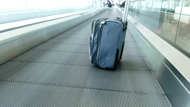 small suitcase rides moving walkway in airport - carry on luggage stock videos and b-roll footage