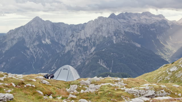 vídeos y material grabado en eventos de stock de tienda ds pequeño poner arriba en la montaña en un prado rocoso y ventoso - tienda de campaña