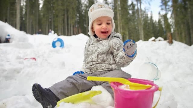 slo mo small toddler sitting in the snow outside next to his brother and having fun - next to stock videos & royalty-free footage