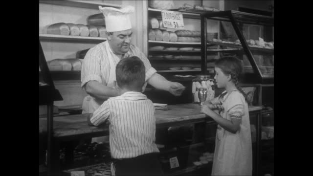 small town america circa 1940 reenactment - bakery, baker serves a boy and girl, gives them cookies. - 1910 stock videos & royalty-free footage
