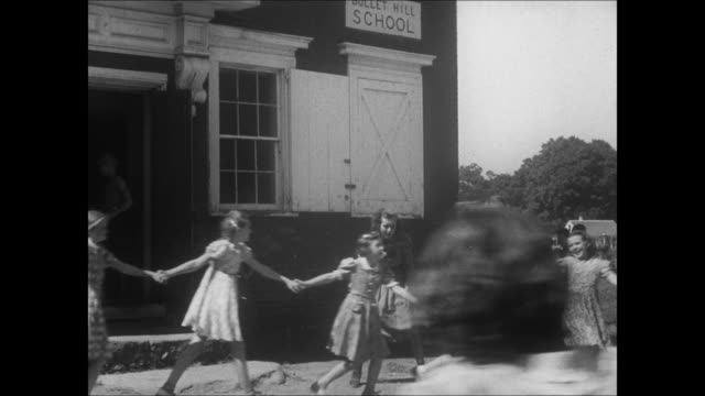 vidéos et rushes de small town america circa 1940 reenactment - children playing outside small schoolhouse, the children all run into school. - l'amérique profonde