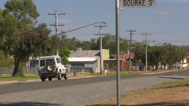 ms pan small town bourke st sign & car running on road / menindee, new south wales, australia - town stock videos & royalty-free footage