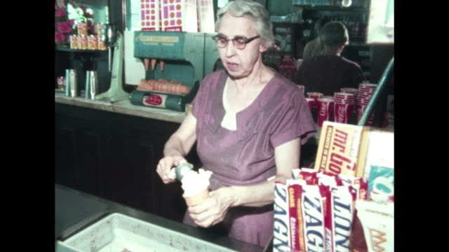 small town main street / young adults enter small store called the welcome corner, woman serves them ice cream. - straßenschild stock-videos und b-roll-filmmaterial